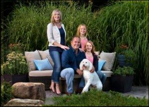 family with white dog poodle mix outdoors professional photoshoot