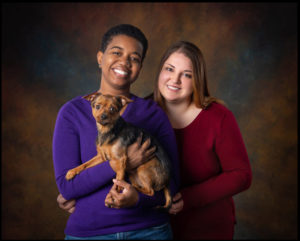 black and white women holding puppy red and brown background professional photoshoot pet studio