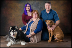 family dad mom and daughter with pets dogs on a classic background professional pet photography